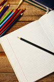 Blank paper and colorful pencils, on the wooden table. View from above. School concept. Stock Photos