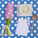 A blank paper, a cup of coffee, and a flower on a table. Time for a break and reflection: a blank paper, a cup of coffee and a Hyacinthus flower on a table with Royalty Free Stock Image