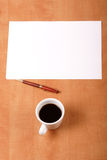 Blank paper, cup of coffee and pen. On the desk - space for copy royalty free stock photo