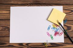 Blank paper and empty yellow square stickers and lot of colored paper clips and one black pencil on old wooden brown worn ta. Blank white paper and empty yellow stock image