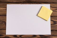 Blank paper and empty yellow square stickers on old wooden brown worn table. Blank white paper and empty yellow square stickers on old wooden brown worn table stock photos