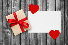Blank paper with gift box and red hearts. On black and white wooden background Royalty Free Stock Photos