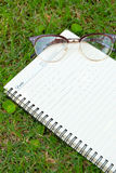Blank paper on green grass. Royalty Free Stock Photos