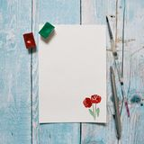 Blank paper with hand painted red roses with copy space on a blue wooden background. Flat lay.  Royalty Free Stock Photography
