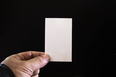 Blank paper in the hands of men. The man is holding a blank paper against a black background Stock Image
