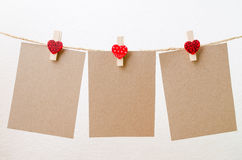 Blank paper hanging on heart clothesline with white background.  Stock Images