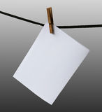 Blank paper hanging on a rope. On a gray background Royalty Free Stock Images