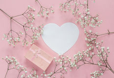 Blank paper heart-card and gift box with frame of delicate little white flowers on pink background from above. Flat lay style. Space for text royalty free stock photography