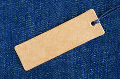 Blank paper label on a blue denim fabric. Jeans background with sale or price tag Stock Photos