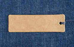 Blank paper label on a blue denim fabric. Jeans background with sale or price tag. Royalty Free Stock Photo