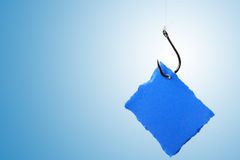 Blank paper label on fishhook over blue background Royalty Free Stock Photography