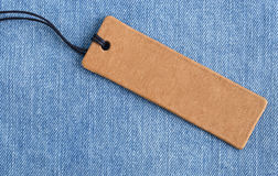Blank paper label on a light blue denim fabric. Jeans background with sale or price tag. Stock Photos