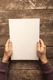 Blank Paper. Man Holding Blank Paper on Wood Table Stock Images