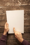 Blank Paper. Man Holding Blank Paper on Wood Table Royalty Free Stock Photos