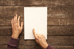 Blank Paper. Man Holding Blank Paper on Wood Table Royalty Free Stock Image