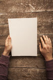 Blank Paper. Man Holding Blank Paper on Wood Table Stock Photography