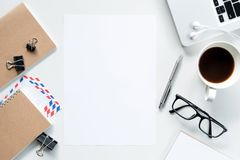 Blank a4 paper is in the middle of white office desk. Top view, flat lay.  royalty free stock photo