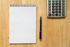 Blank paper note book with pen, calculator. On wood table Royalty Free Stock Image
