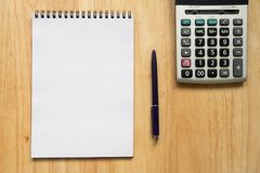 Blank paper note book with pen, calculator on wood table. Background Stock Image
