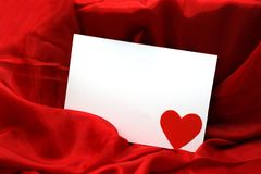 Blank paper note card with red heart on red silk fabric background. stock photography