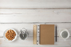 Blank paper note with coffee and alarm clock on white wood table Royalty Free Stock Photography