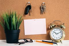 Blank paper note on cork board with car key, golden alarm clock, reading glasses, pen and green plant in pot. Memo and time management concept. blank note for Royalty Free Stock Images
