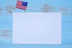 Blank paper note with  flag of the United States of America on blue wooden background. USA holiday of Veterans, Memorial, stock image