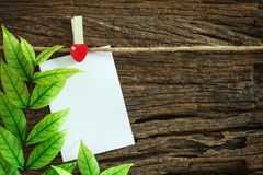 Blank paper note hanging by red heart clips on wooden background Royalty Free Stock Photography