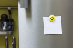 Blank paper note with magnet hanging on fridge door Royalty Free Stock Images