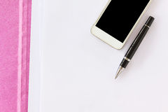Blank paper note with pen on business file folder and cellphone. Background with copyspace Royalty Free Stock Images