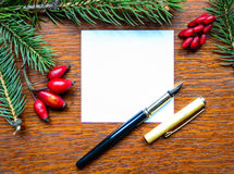 Blank paper note with pen and Christmas tree branches on wooden. This image represents the Blank paper note with pen and Christmas tree branches on wooden Stock Photography