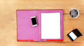 Blank paper note with pen on document file on work table. Blank paper note on file folder and mobile phone on wood table with cup of hot black coffee and empty Stock Photography