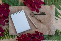 Blank paper note, pencil and vintage key on wooden table decorated with red orchid and green fern stock photos