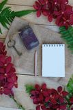 Blank paper note, pencil and vintage key on wooden table decorated with red orchid and green fern royalty free stock photo