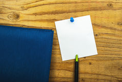 Blank paper note on wood background with blue pin and diary book Stock Photo