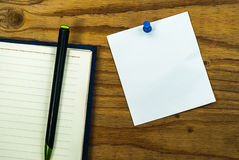 Blank paper note on wood background with blue pin and diary book Royalty Free Stock Photo