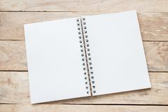 Blank paper notebook on brown wooden table background. Top view with copy space selective focus stock image