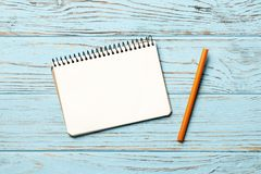 paper notebook with pen on blue wooden background stock images
