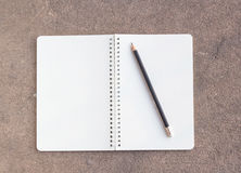 Blank paper notebook and pencil on cement floor background. Royalty Free Stock Image
