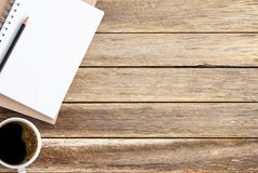 Blank paper notebook,pencil and coffee on brown wooden table background. stock photos