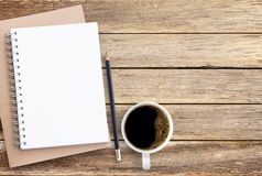 Blank paper notebook,pencil and coffee on brown wooden table background. royalty free stock image