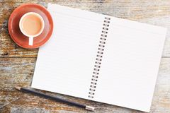 Blank paper notebook with pencil and cup of coffee on wooden tab. Office desk table- Blank paper notebook with pencil and cup of coffee on wooden table.View from Stock Photo