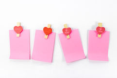 Blank paper notes and heart shaped clips, theme for Valentine`s day Royalty Free Stock Images