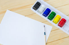 Blank paper with paintbrush and primary colors Stock Photography
