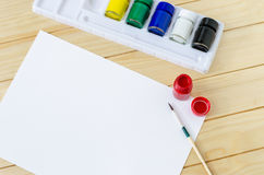 Blank paper with paintbrush and primary colors Royalty Free Stock Photo