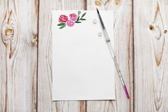 Blank paper with painted roses with the place for your text on a wooden background. Stock Images