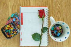 Blank paper, paper clip and rose on wooden. View from above Royalty Free Stock Photography