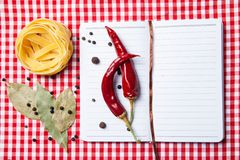 Blank paper with pasta, pepper and spices. Blank paper for recipes with ingredients, pasta, pepper and spices on red tablecloth Royalty Free Stock Photos