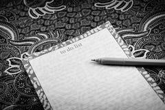Batik. Blank paper and pen on batik background. black and white royalty free stock image