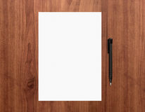 Blank paper with pen on desk. Blank white paper with pen on a wooden desk. High quality graphic collage